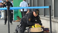 A Philippine police bomb disposal unit member inspects an abondoned luggage at the departure area of the airport in Manila on September 1, 2014.