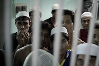 This picture taken on February 14, 2013 shows Muslim Rohingha asylum seekers standing inside a cell at the Thai immigration detention centre in Phangnga, southern Thailand.