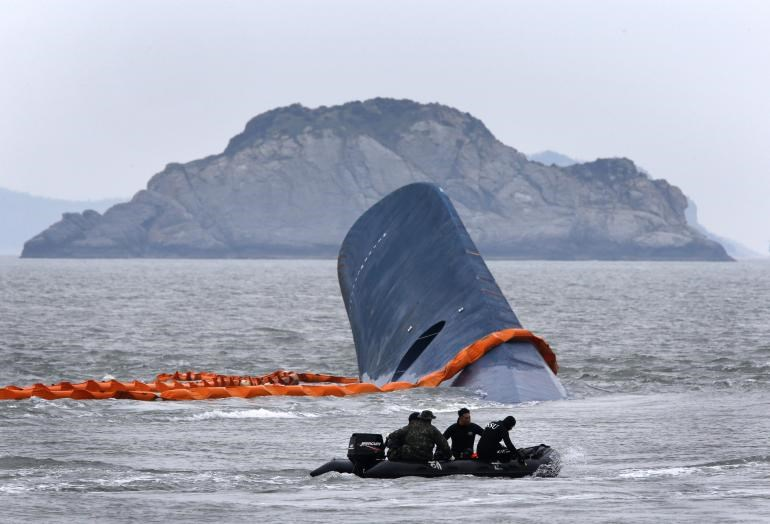 "A vessel involved in salvage operations passes near the upturned South Korean ferry ""Sewol"" in the sea off Jindo April 17, 2014."