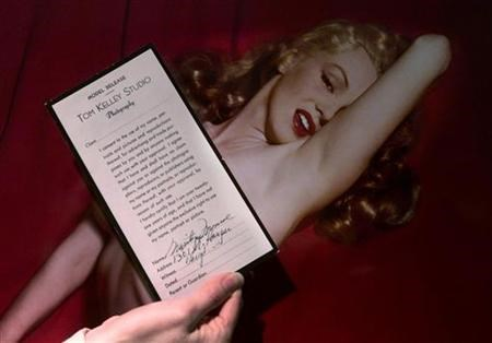 An employee of Butterfields auction house displays a copy of a model release signed by Marilyn Monroe in front of one of the photographs of Monroe during a Hollywood photo shoot in 1949, in Los Angeles, March 22, 2001. A 15-minute film of Marilyn Monroe e