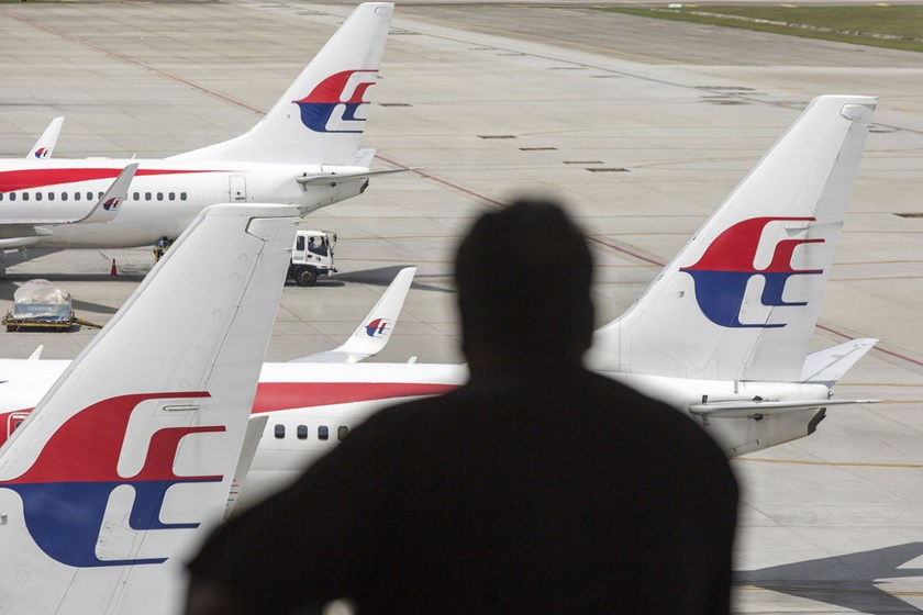 A man looks out at the aircrafts operated by Malaysian Airline System Bhd. standing on the tarmac at Kuala Lumpur International Airport in Sepang, Malaysia. The airline has suffered two disasters this year that claimed the lives of 537 people.