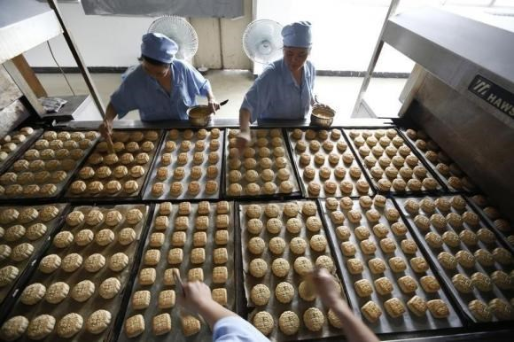 Freshly-baked mooncakes pass along a conveyor belt at a mooncakes factory in Shanghai September 12, 2013.