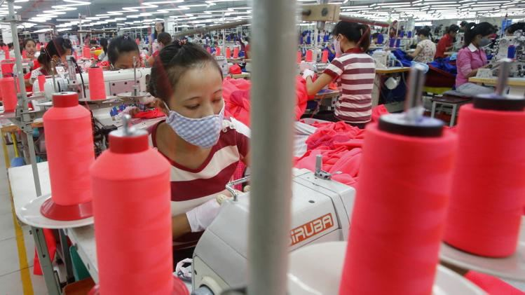Labourers work at an assembly of Singapore's invested Singlun Star garment factory outside Hanoi August 19, 2014.