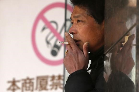 A man smokes in front of a ''no smoking'' sign outside a shopping mall in Shanghai in this January 10, 2014 file photo.