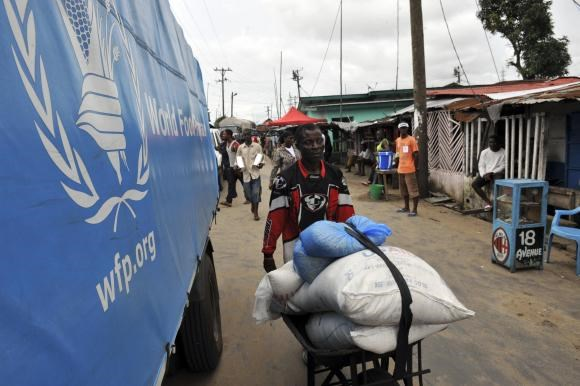 A resident of West Point neighborhood, which has been quarantined following an outbreak of Ebola, pushes a wheelbarrow full of food rations from the United Nations World Food Programme (WFP) in Monrovia August 28, 2014.