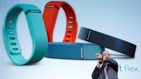 Masayoshi Son, president of SoftBank Corp., demonstrates a Fitbit Flex wearable device. Photo: Bloomberg