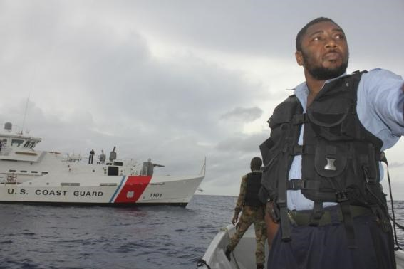 A member of the Jamaica Defence Force stands on their vessel next to a US Coast Guard cutter during the search for the plane belonging to real estate executive Larry Glazer offshore of Port Antonio, September 6, 2014.