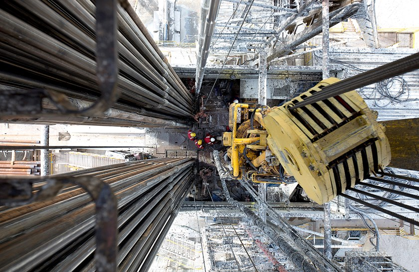 Oil workers operate drill sections while working on the drilling floor beneath the travelling block, right, on a derrick operated by Salym Petroleum in Salym, Khanty-Mansi autonomous region, Russia.