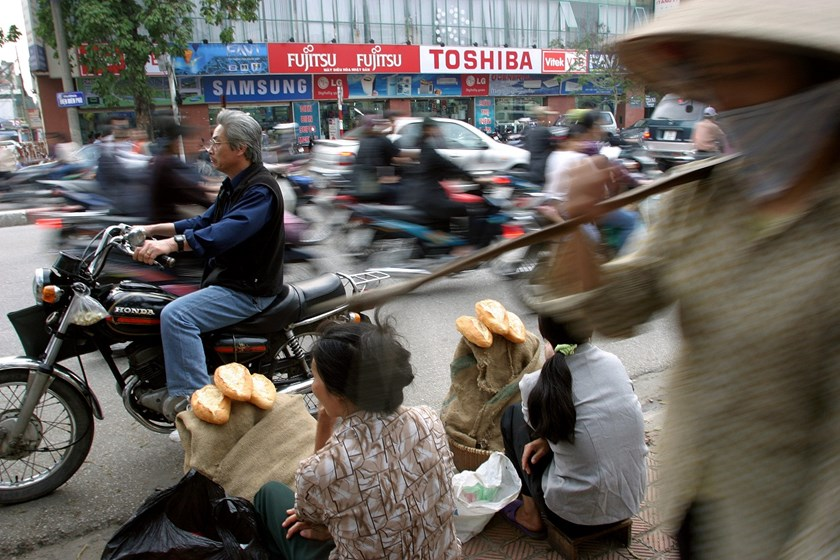 Street vendors sell bread in front of a big electronic supermarket, while motorbikes and cars pass by in Hanoi, Vietnam.