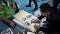 Workers unwrap logos for Volkswagen AG and China FAW Group Corp. during preparations ahead of the 11th China (Guangzhou) International Automobile Exhibition in Guangzhou, China.
