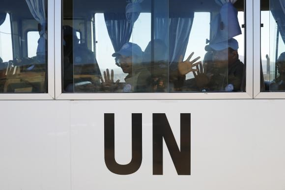 Fijian U.N. peacekeepers released by al-Qaeda-linked group Nusra Front in Syria on Thursday, gesture from inside a vehicle as they arrive in Israeli-held territory on the Golan heights September 11, 2014.