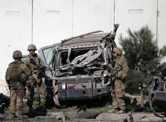 U.S. troops keep watch near a damaged vehicle at the site of suicide attack in Kabul September 16, 2014.