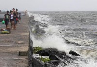 Youth walk on breakwater where rough waves caused by Typhoon Kalmaegi, also called Luis, are crashing, at Manila Bay September 14, 2014.
