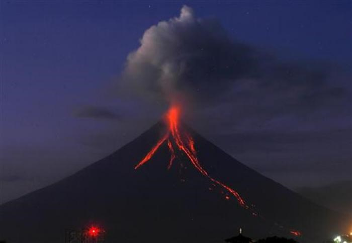 Mayon Volcano spews ash as glowing lava cascades down its slope during a mild eruption on December 24, 2009.
