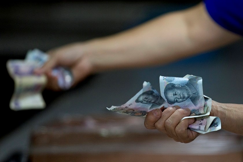 Customers hold Chinese yuan banknotes while shopping inside a wet market in the Sanlitun area of Beijing, China.