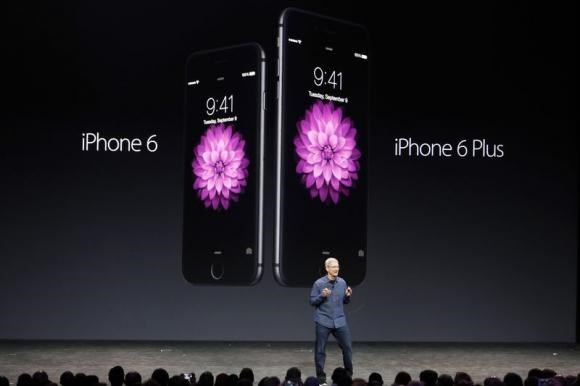 Apple CEO Tim Cook introduces the new iPhone 6 and iPhone 6 Plus (R) during an Apple event at the Flint Center in Cupertino, California, September 9, 2014.