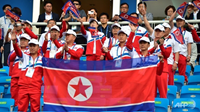 North Korean delegation members wave the national flags before the first round of the men's football match between North Korea and China during Day 4 of the 17th Asian Games in Incheon, South Korea. Photo: AFP