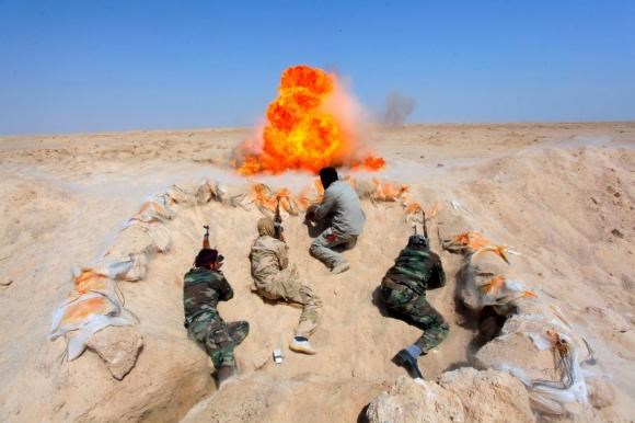 Shi'ite fighters, who have joined the Iraqi army to fight against militants of the Islamic State, formerly known as the Islamic State of Iraq and the Levant, take part in field training in the desert in the province of Najaf, September 16, 2014.