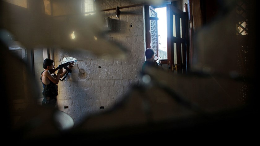 Rebel fighters aim their weapons during clashes with government forces in the Syrian city of Aleppo, on July 21, 2014.