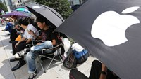 Customers sit under umbrellas as they wait in line outside Apple Inc.'s Ginza store ahead of the launch of the company's new iPhone 6 and iPhone 6 Plus in Tokyo, Japan.