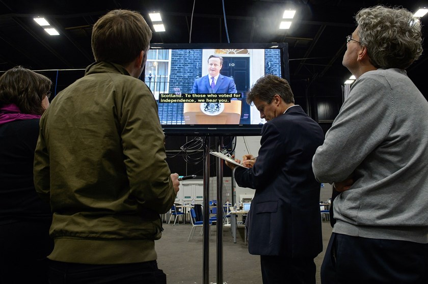 Journalists listen to a televised address by British Prime Minister David Cameron following referendum results at the Royal Highland Centre in Edinburgh, Scotland, on Sept. 19, 2014.