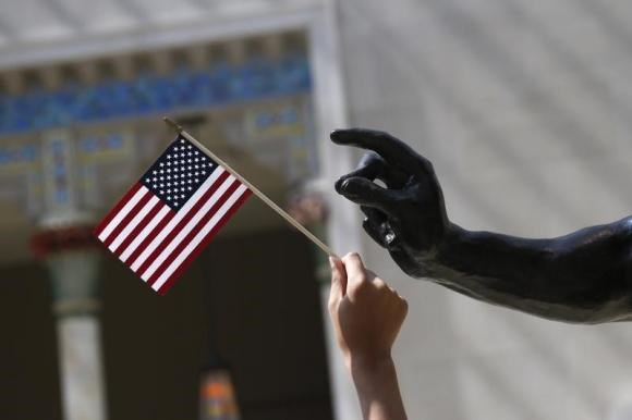 A girl holds a U.S. flag next to a sculpture after a naturalization ceremony in New York July 22, 2014.