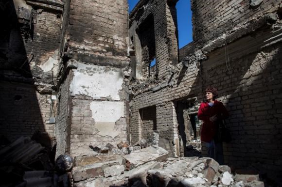 A woman stands inside her destroyed home in the town of Ilovaysk, eastern Ukraine, September 19, 2014.