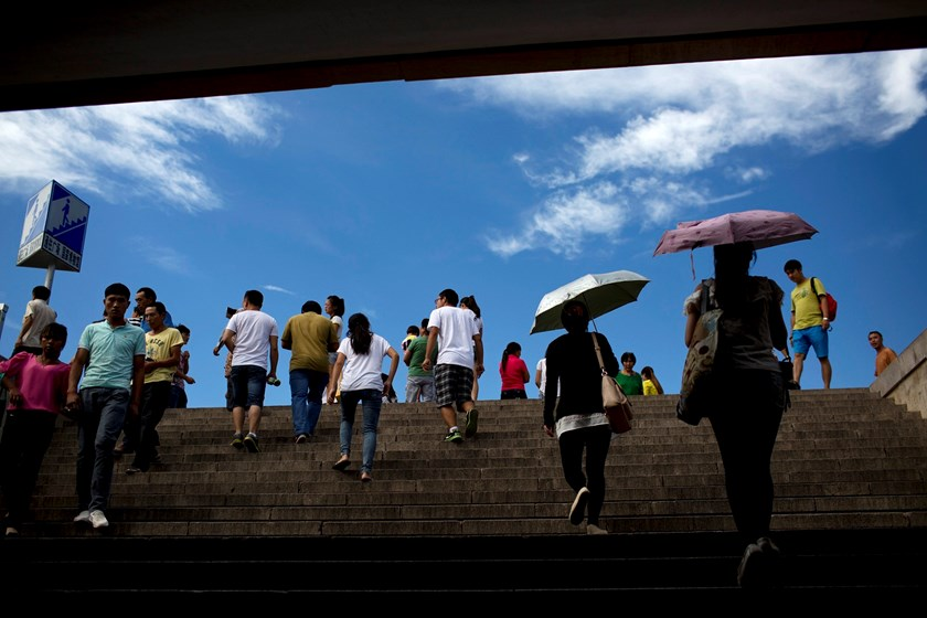 People walk up a flight of steps from a pedestrian underpass towards Tiananmen Square in Beijing, China.