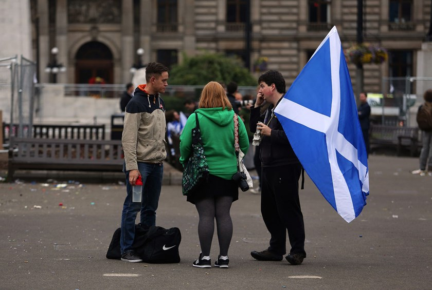 A pedestrian holds the national flag of Scotland following Scottish independence referendum result night celebrations in George Square in Glasgow, U.K., on Sept. 19, 2014.