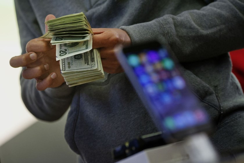 A customer counts cash to pay for two iPhone 6 smartphones during the sales launch at the Apple Inc. store in New York, U.S., on Friday, Sept. 19, 2014.