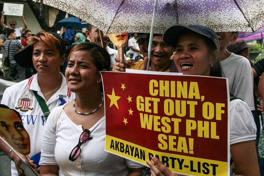 A group of protesters chant slogans against the Chinese incursions within the South China Sea in Makati, Philippines.