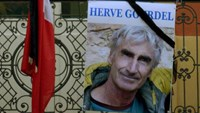 A portrait of mountain guide of Frenchman Herve Gourdel hangs near a French flag outside the town hall in Saint-Martin-Vesubie, September 24, 2014.