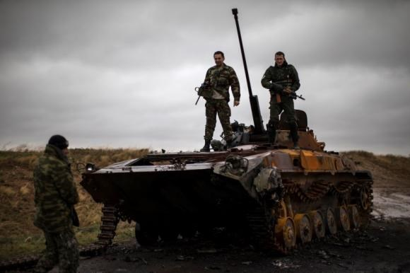 Ukrainian rebels stand on top of a burnt-out Ukrainian armoured personnel carrier near the village of Novokaterinovka, eastern Ukraine, September 24, 2014.
