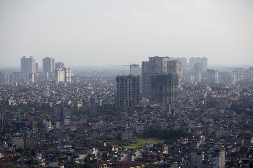 Cranes operate at a residential construction site, center right, in Hanoi.