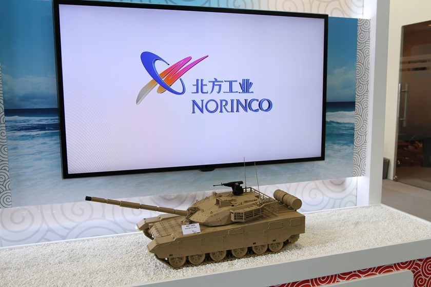 A model of an MBT-3000 Main Battle Tank stands in front of a demonstration screen at the China North Industries Group Corp. (Norinco) trade stand during the Africa Aerospace & Defence Show at the Waterkloof Air Force Base in Pretoria, South Africa, on Sep