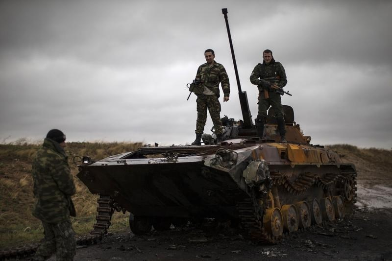 Pro-Russian rebels stand on top of a burnt-out Ukrainian armoured personnel carrier near the village of Novokaterinovka, eastern Ukraine, September 24, 2014.