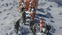 Japan Self-Defense Force (JSDF) soldiers and firefighters carry an injured person near a crater of Mt. Ontake, which straddles Nagano and Gifu prefectures in this September 28, 2014 photo taken and released by Kyodo.