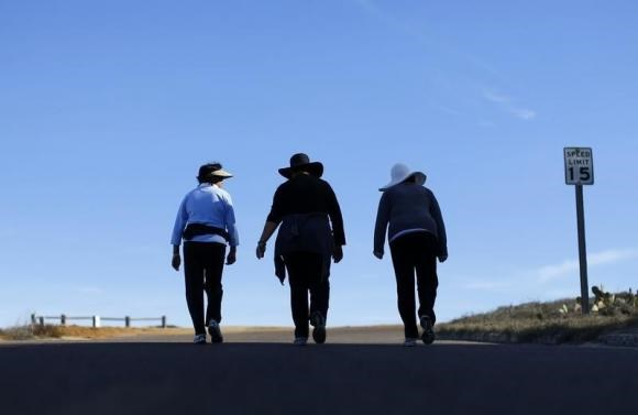 Women walk together up a hill as they participate in some morning exercise during a visit to Torrey Pines State Park in San Diego, California, November 14, 2012.