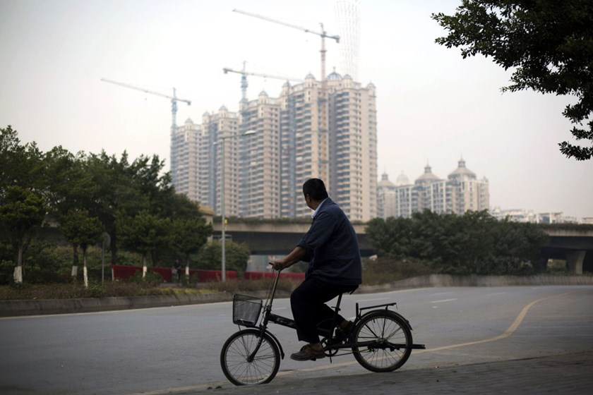 Man on bicycle in passes construction site in China.