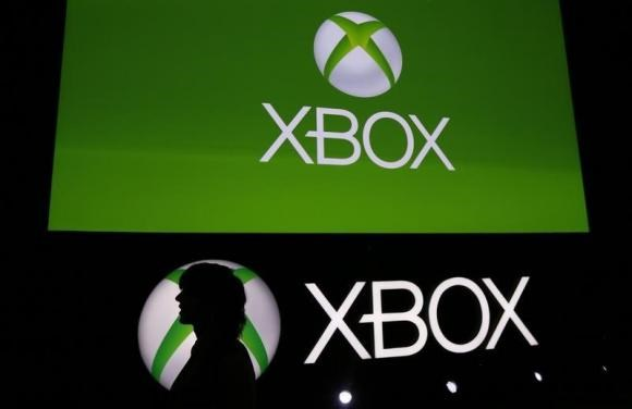 A Spanish Games blogger is silhouetted against the logo of Microsoft's Xbox during the Xbox Play Day 2014, before the Gamescom 2014 fair in Cologne August 12, 2014.