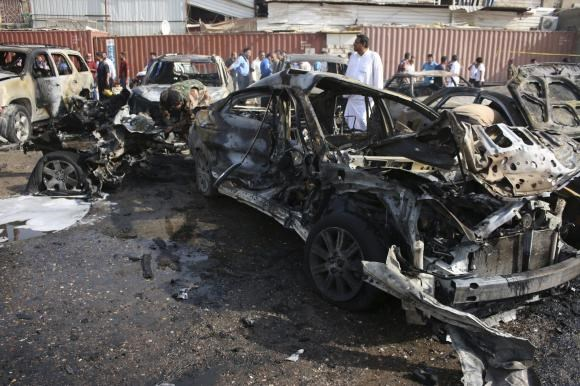 People inspect the site of a car bomb attack in Basra, southeast of Baghdad September 30, 2014. The car bomb attack took place in a parking lot and no one was hurt, police sources said.