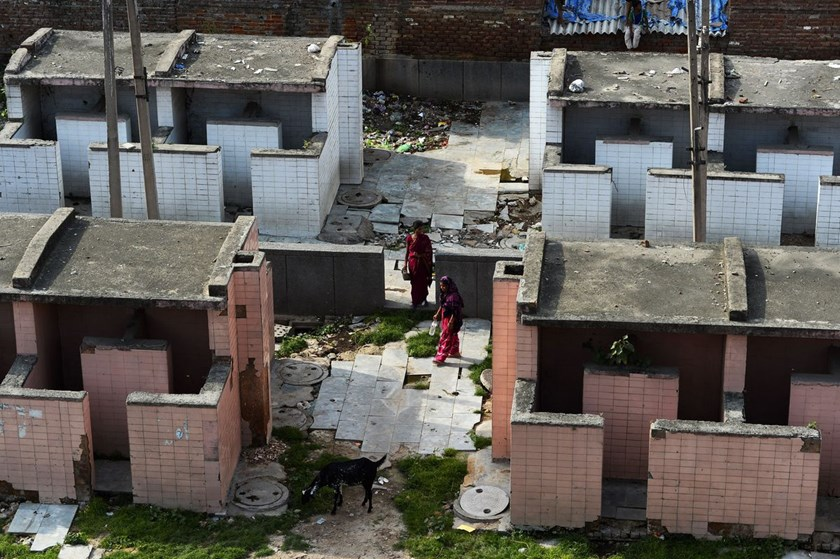 Indian residents leave a public toilet block in New Delhi on Aug. 16, 2014.
