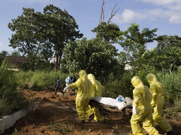 A burial team wearing protective clothing prepare the body of a person suspected to have died of the Ebola virus for interment, in Freetown September 28, 2014.