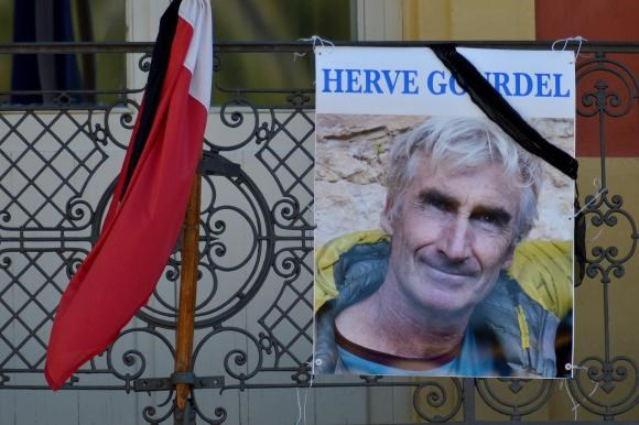 A portrait of mountain guide Frenchman Herve Gourdel hangs near a French flag outside the town hall in Saint-Martin-Vesubie, September 25, 2014.
