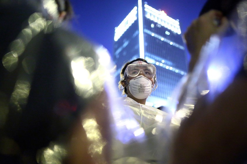 A demonstrator dressed in a rain court and protective goggles stands in front of the gate leading to the office of Hong Kong's chief executive Leung Chun-ying in Hong Kong, China, on Oct. 2, 2014.