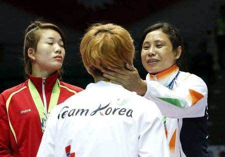 India's bronze medallist Laishram Sarita Devi reacts during the medal ceremony for the women's light (57-60kg) boxing competition at the Seonhak Gymnasium during the 2014 Asian Games in Incheon .