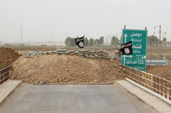 Islamic State flags flutter on the Mullah Abdullah bridge in southern Kirkuk September 29, 2014.
