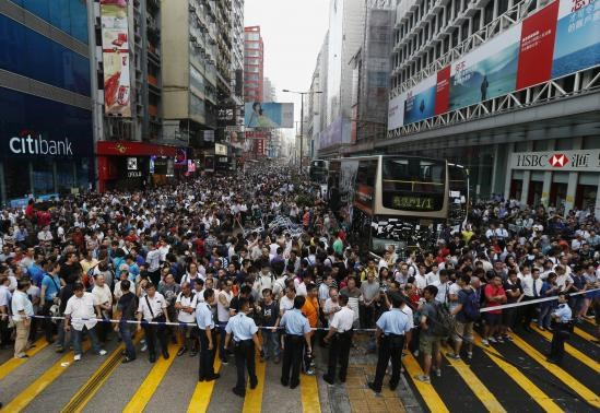 Anti-Occupy Central protesters stand behind a police cordon on Nathan Road at Hong Kong's Mongkok shopping district October 3, 2014, demanding the tents set up by pro-democracy protesters to be demolished.