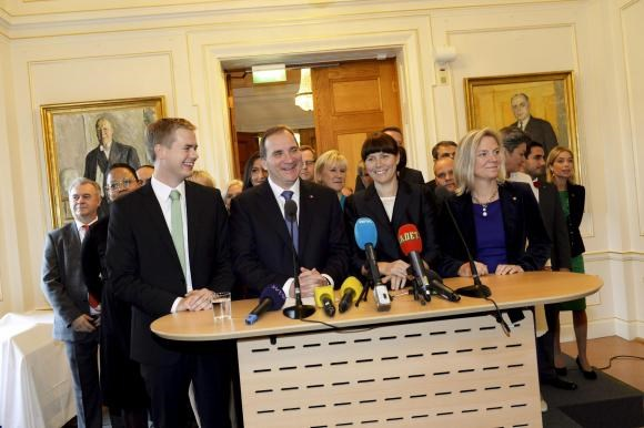 Swedish Prime Minister Stefan Lofven (front 2nd L) smiles as he stands with his new government during a news conference in Stockholm October 3, 2014.