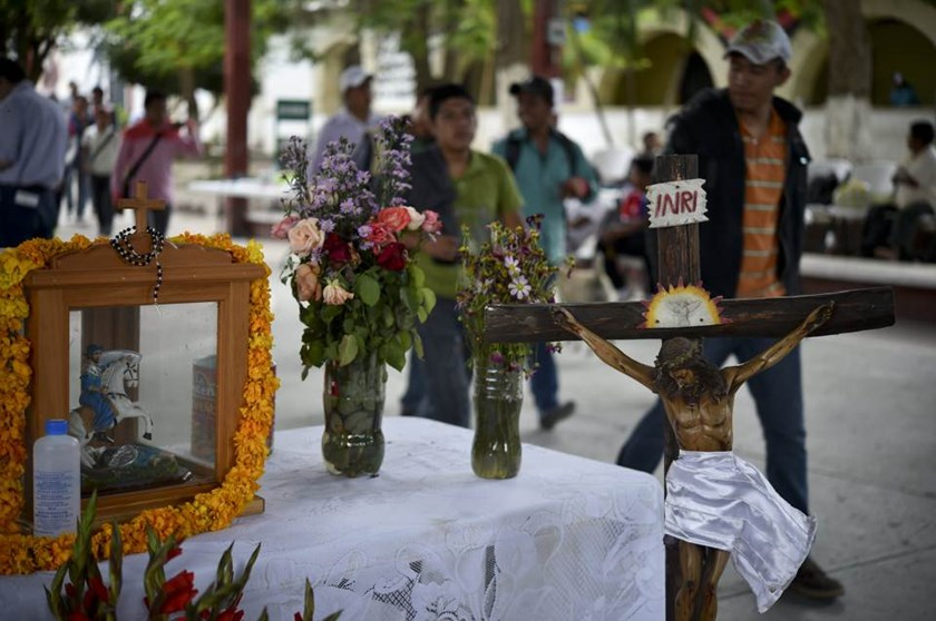 Students walk past an altar in memory of killed and missing peers in Ayotzinapa, Guerrero state, Mexico on October 5, 2014